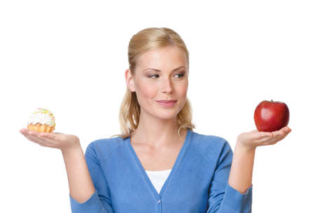 deciding: Pretty woman makes a tough choice between cake and apple, isolated on white