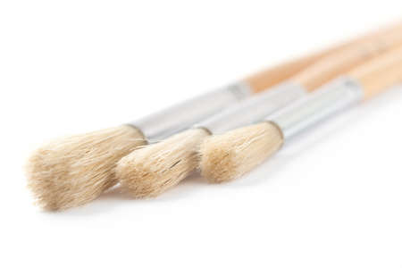 Three bright brushes are lying close to each other on white background, isolated photo