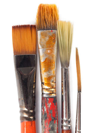 Four dirty brushes are lying on white background, isolated on white photo