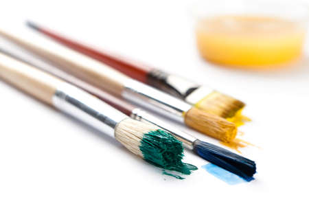 Set of brushes stained with paint near the ink container photo