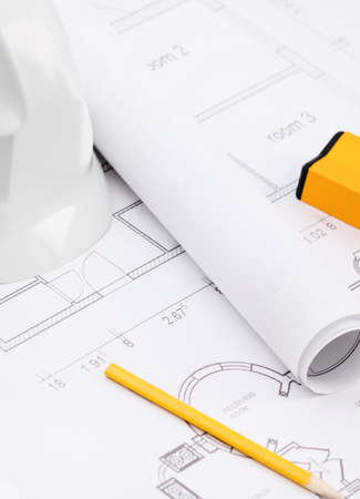 engineer's: White hard hat near working drawings, pencil, level for building needs
