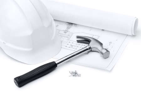 building material: White hard hat, hammer on the druft and nails, isolated on white