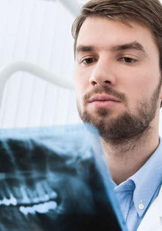 profundity: Dentist carefully examines the x ray image, white background