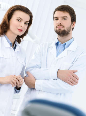 Dentist and his assistant welcome the patient to the dental clinic, white background photo