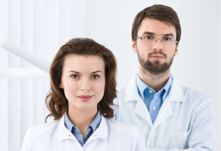profundity: Dentist and his assistant is waiting for the patient, white background