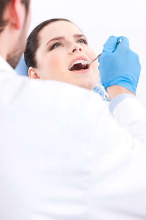 Dentist in blue medical gloves examines the oral cavity of the patient, white background photo