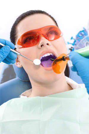 Dentist uses photopolymer lamp and dental mirror to treat carious teeth of the patient photo