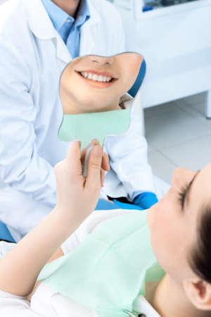 gladly: El paciente admira su sonrisa mirando al espejo despu�s del tratamiento