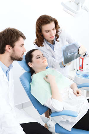 Dentist and his assistant explain details of the x ray image to the patient, white background photo