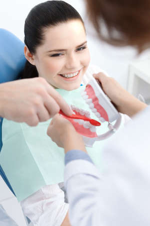 profundity: Dentist and his assistant teach the patient how to clean teeth correctly