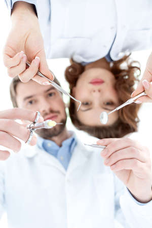 Dentist and his assistant show different medical instruments photo