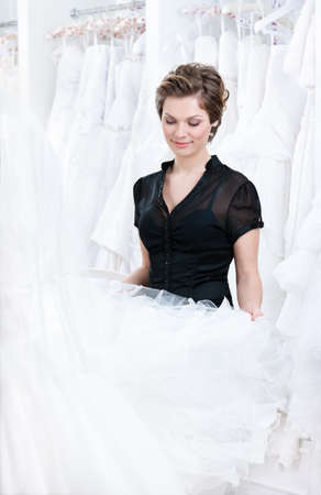 Shop assistant wants to select a proper dress for the client, on white background. photo