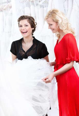 hesitating: Dos ni�as de discutir el vestido de novia dudando de adaptaci�n. Fondo blanco