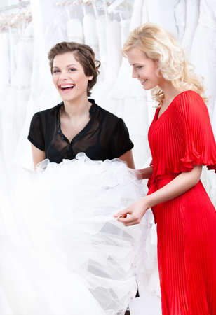 Two girls discuss the wedding dress hesitating about fitting. White background photo