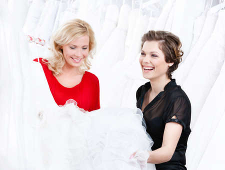 Designer and the client have a good look at the wedding dress preparing to try it on. Stock Photo - 14649699