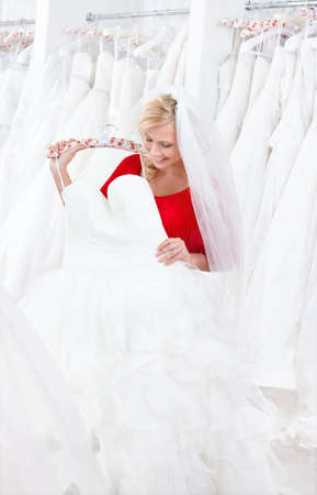 Bride is looking forward to try wedding dress on, on white background. photo
