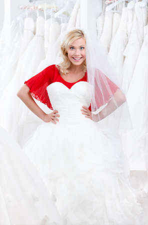 Agitated girl puts a wedding gown to her body, deciding whether it suits for her or not photo