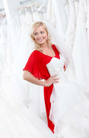 Young girl puts a wedding gown to her body, deciding whether it cuts to her or not photo