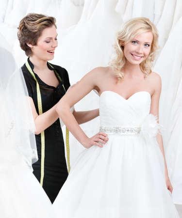 lanzamiento de bala: Costurera ajusta el vestido de la novia, fondo blanco
