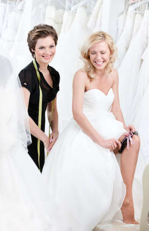 Laughing future bride in wedding gown puts the garter photo