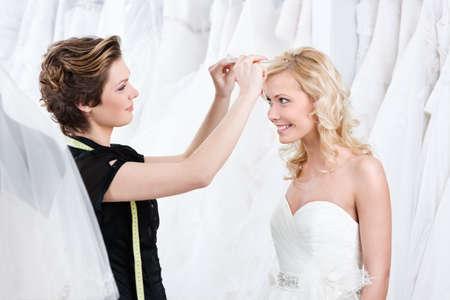 lanzamiento de bala: Dependiente de la tienda ayuda a fijar la tiara de la boda, fondo blanco Foto de archivo