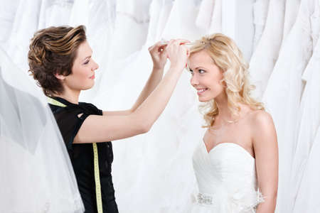 Shop assistant helps to fix the wedding tiara, white background photo