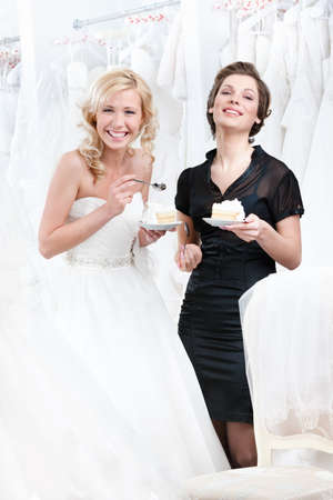 Laughing shop assistant and the bride eat a delicious cake selebrating a good decision photo