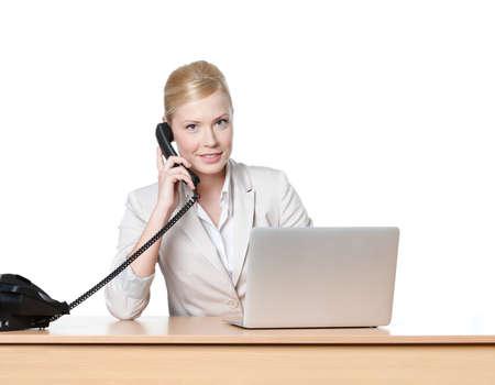 phone handset: Donna d'affari giovane seduto a un tavolo ufficio e tenendo premuto cornetta del telefono, isolato