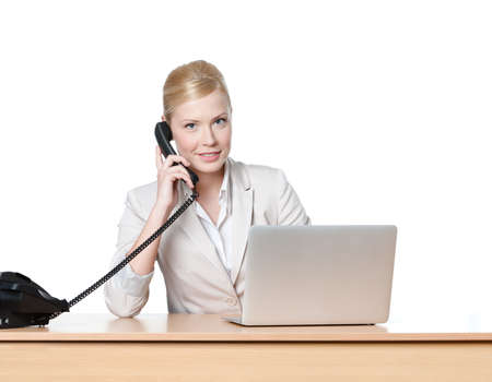 fax: Young business woman sitting at a office table and holding phone handset, isolated Stock Photo