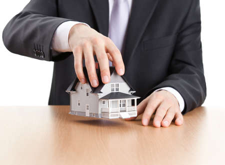 Real estate concept - businessman holding house architectural model photo