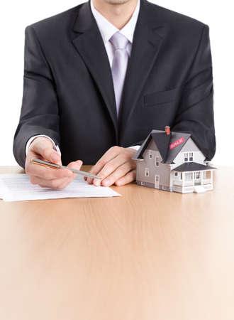 contratos: Concepto de bienes ra�ces - hombre de negocios firma un contrato detr�s de la casa modelo de arquitectura Foto de archivo