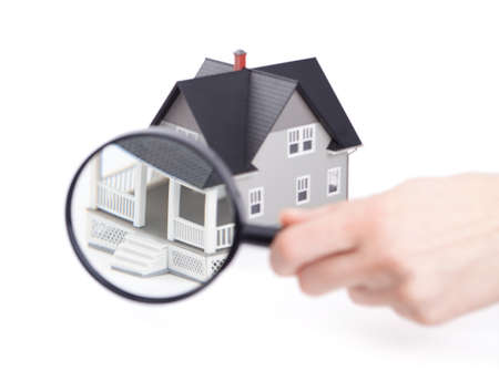 Real estate concept - hand holding magnifying glass in front of the home architectural model, isolated Stock Photo - 14661076