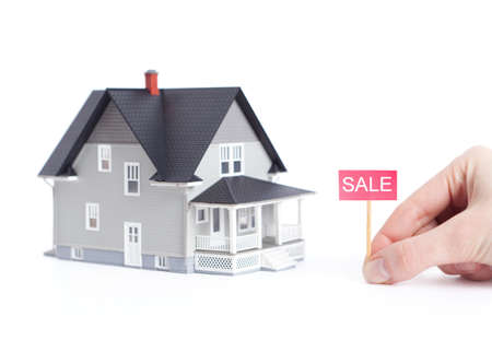 hand holding house: Real estate concept - household architectural model with sale sign, isolated