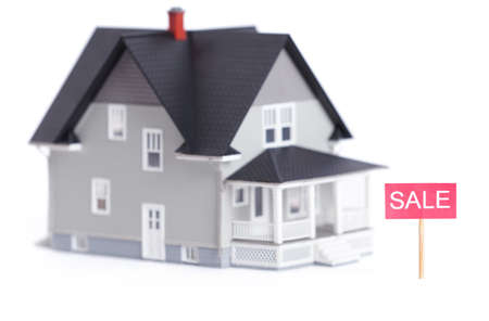 Real estate concept - home model with sale sign, isolated Stock Photo - 14661093