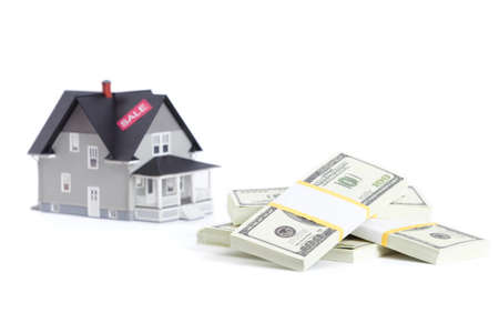 Real estate concept - bundles of dollars in front of home architectural model, isolated Stock Photo - 14661081