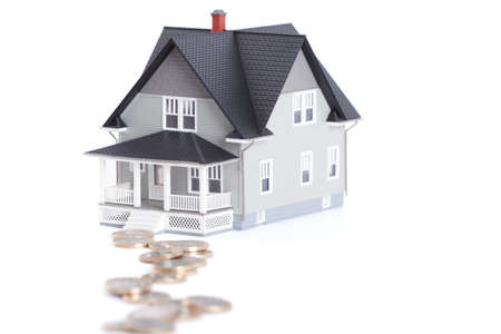 Real estate concept - coins in front of home architectural model, isolated Stock Photo - 14661094
