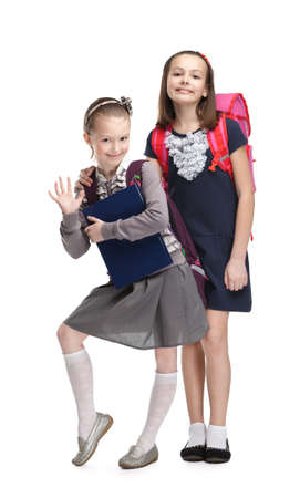 school uniform girl: Two little girls are happy to start new year of study, isolated, white background