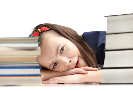 Pupil is yawning around the pile of books, isolated, white background photo