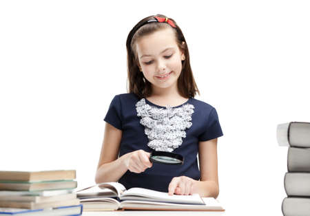 schoolgirl uniform: Little schoolgirl wonders about interesting details in the book, isolated, white background Stock Photo