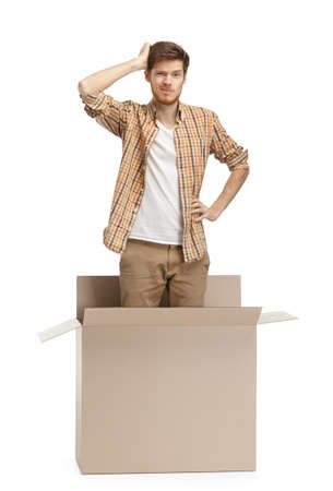 Young man wonders why he is inside the box, isolated, white background photo