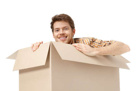 Pretty man hides inside the cardboard box, isolated, white background Stock Photo - 14649728