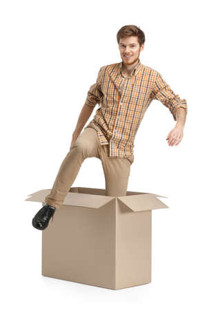 Young man comes out of the cardboard box, isolated, white background photo