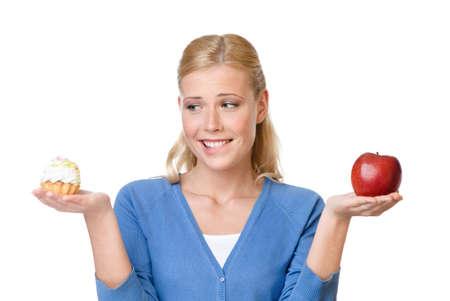 toma de decision: Mujer atractiva que hace que una elecci�n dif�cil entre la torta y la manzana, aislado