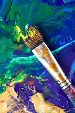 Painting some picture with paintbrush using mixture of blue, green, yellow, violet colors, white background photo