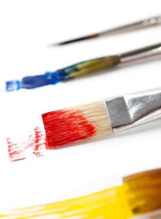 Paintbrushes with varied ink are lying on white background, isolated photo