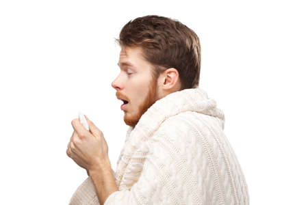 achy: Sneezing young man holding wipes in his hands, isolated Stock Photo