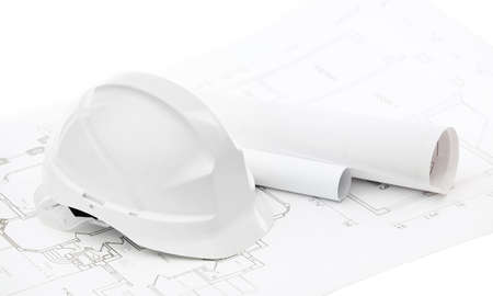 architecting: White hard hat near working drawings on white background