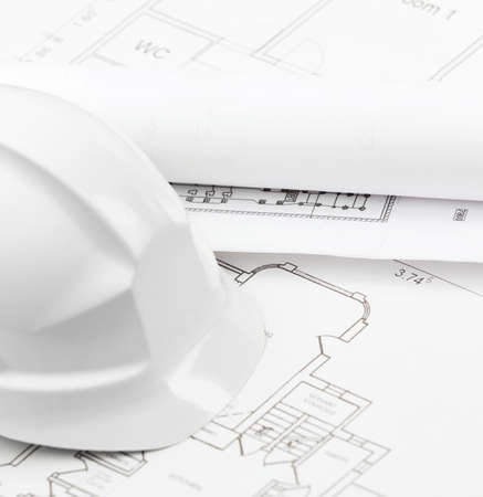 hard stuff: White hard hat on several working or engineering drawings on white background Stock Photo