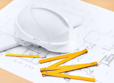 White hard hat near working drawings, pencil, rule for building needs Stock Photo
