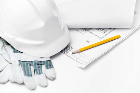 maintenance engineer: White hard hat on the gloves and pencil on the druft, isolated on white background